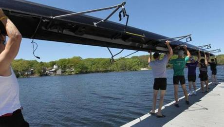Holy Cross crew lifts boat into Lake Quinsigamond.